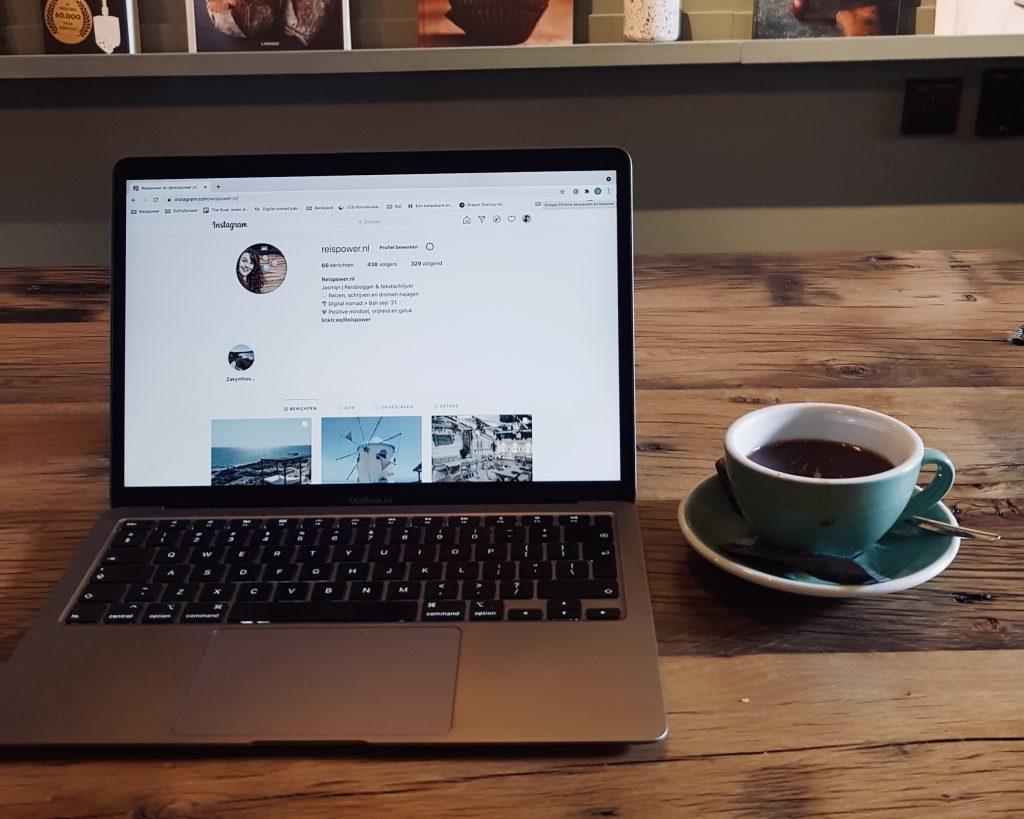 MacBook naast kopje koffie in een café